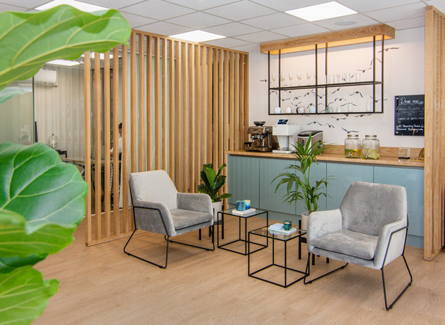 The coffee bar station with an art mural of flying birds in the waiting area of the reception at Banning Dental Group