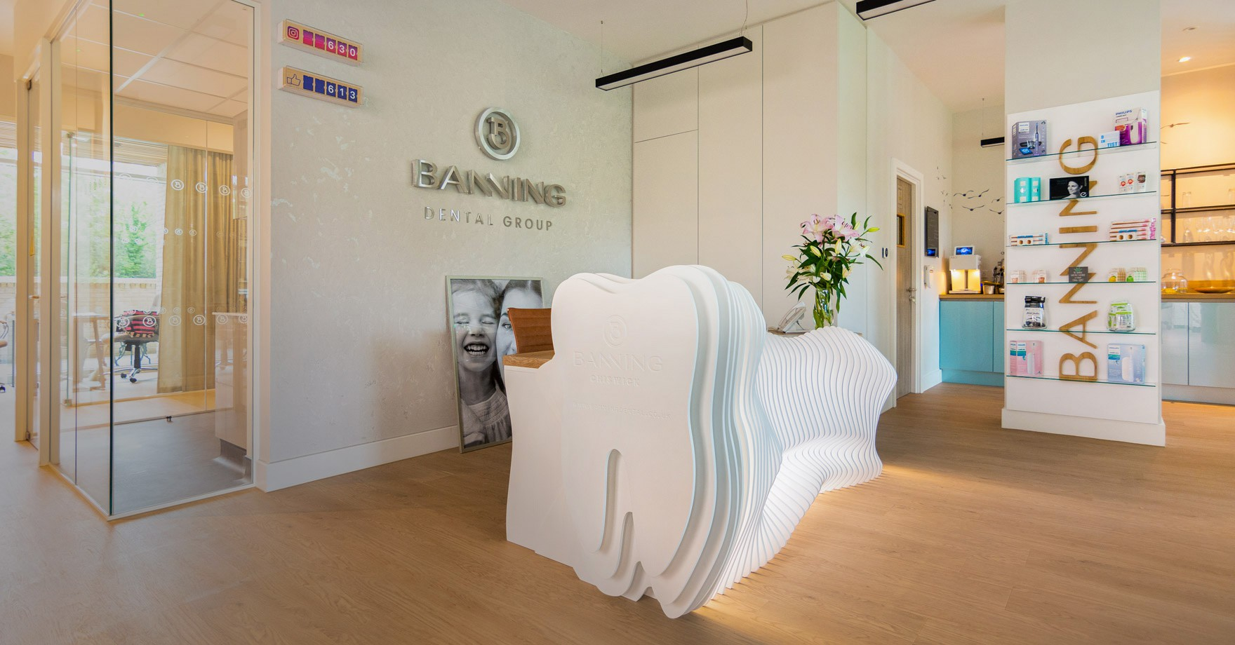 Banning Dental Group reception area design with bespoke desk in the shape of a tooth with Banning Dental logo in silver planted on the wall.