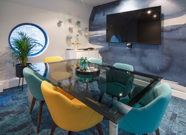 One of the Ibis meeting rooms with blue walls and carpet, a glass rectangular table and turquoise and yellow chairs