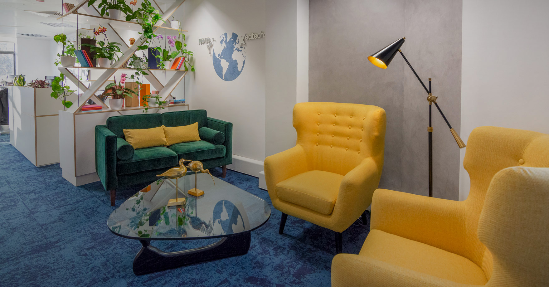 Ibis reception area design, a velvet dark green two seater sofa and bright yellow armchair with a glass table in the middle.