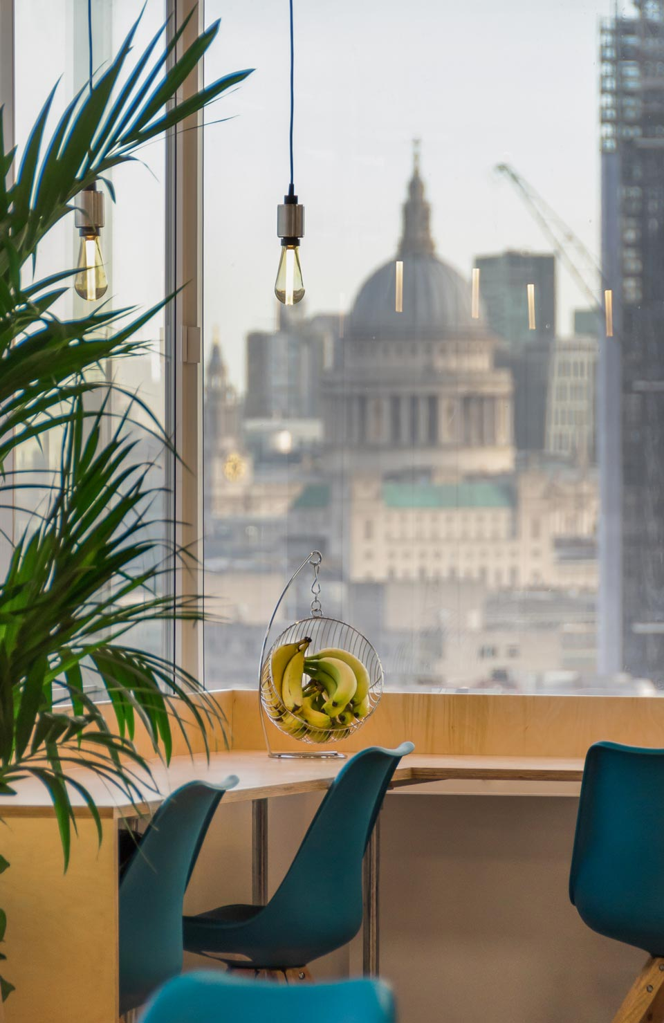 InfoTrack breakout bench tables design that look out to a view of St. Pauls Cathedral in London