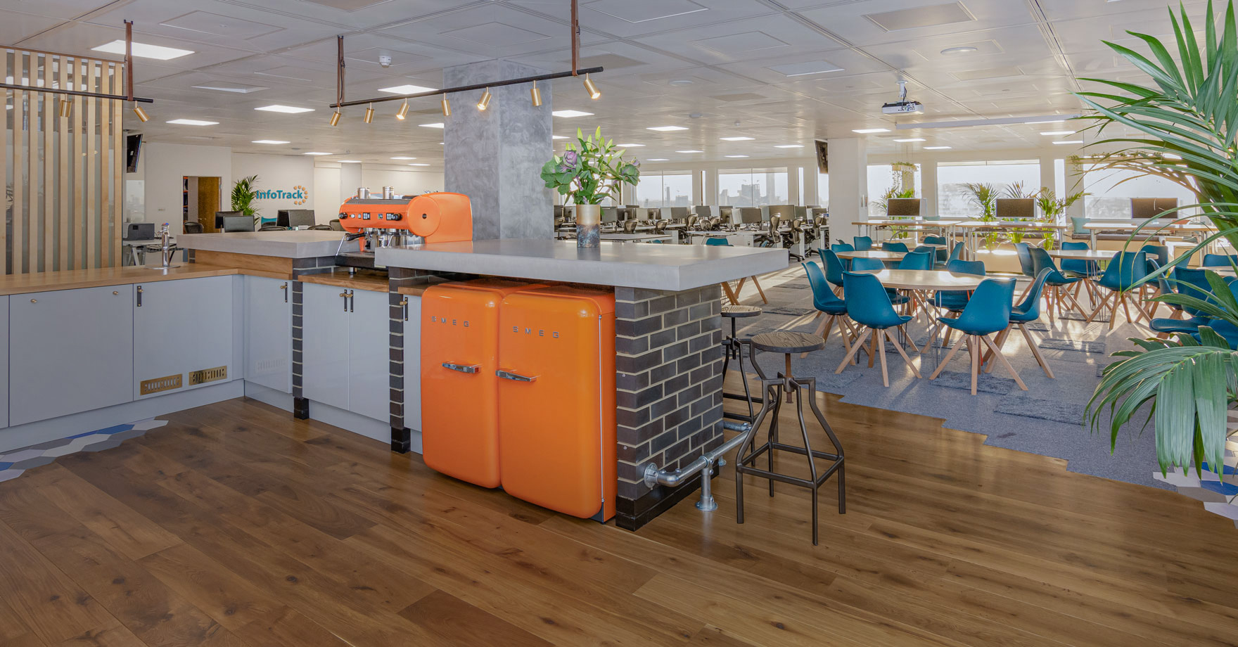 InfoTrack kitchen area and breakout design with Smeg orange appliances and in the background is the rest of the workspace design